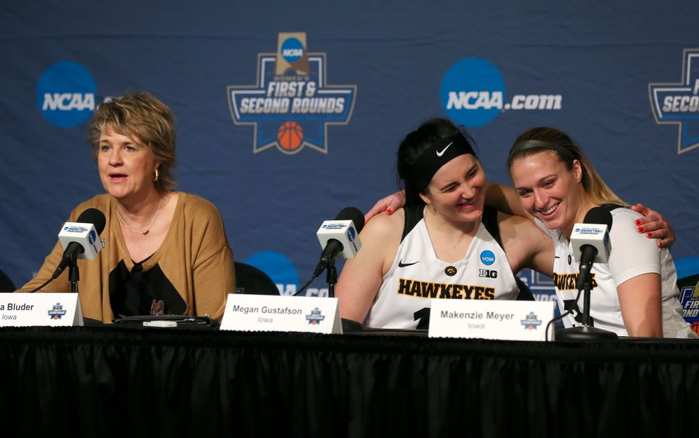Iowa Hawkeyes forward Megan Gustafson (center) and guard Makenzie Meyer (right) hug as head coach Lisa Bluder talks during their press availability after winning their game in the first round of the 2019 NCAA Women's Basketball Tournament at Carver Hawkeye Arena in Iowa City on Friday, Mar. 22, 2019. (Stephen Mally for hawkeyesports.com)