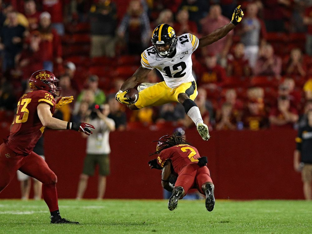 Iowa Hawkeyes wide receiver Brandon Smith (12) hurdles a defender during the third quarter of their Iowa Corn Cy-Hawk Series game at Jack Trice Stadium in Ames on Saturday, Sep 14, 2019. (Stephen Mally/hawkeyesports.com)