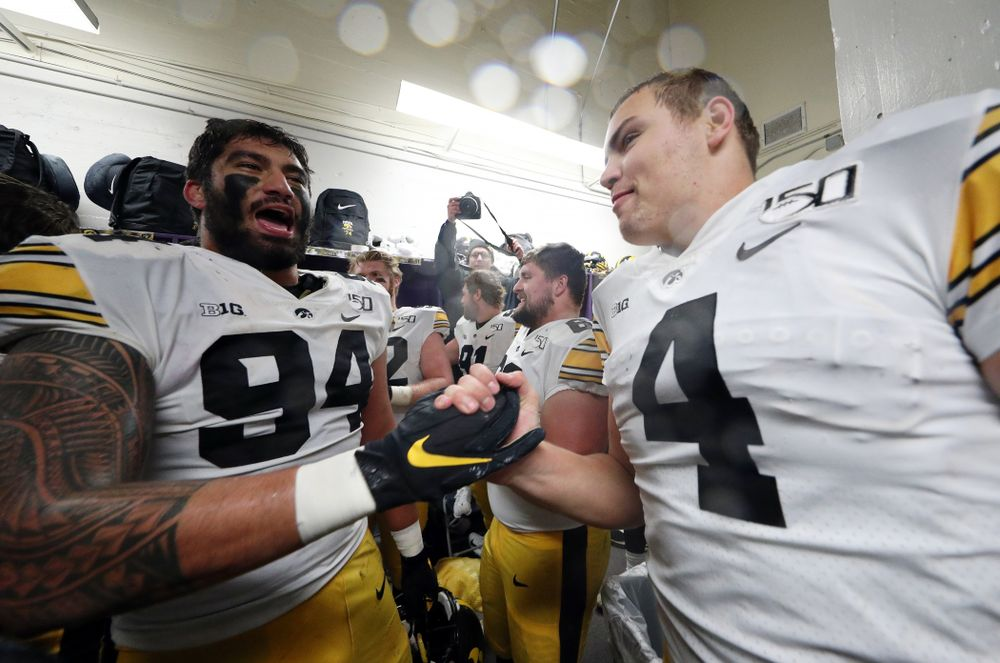 Iowa Hawkeyes defensive end A.J. Epenesa (94) and quarterback Nate Stanley (4) celebrate their victory against the Northwestern Wildcats Saturday, October 26, 2019 at Ryan Field in Evanston, Ill. (Brian Ray/hawkeyesports.com)