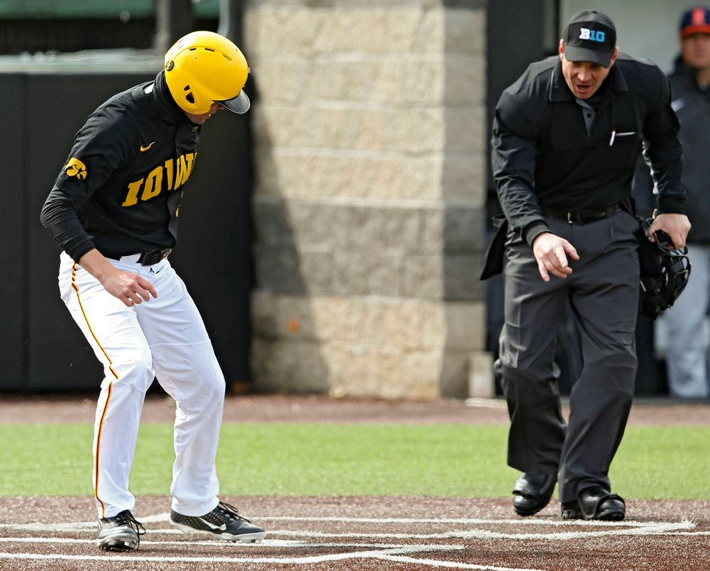 Iowa Hawkeyes right fielder Ben Norman (9) scores a run as the home plate umpire signals that the Illinois catcher blocked the plate during the second inning of their game against Illinois at Duane Banks Field in Iowa City on Saturday, Mar. 30, 2019. (Stephen Mally/hawkeyesports.com)