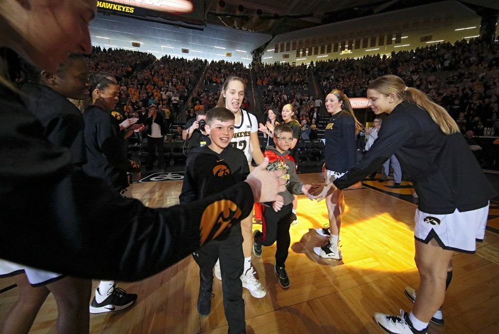 Iowa Hawkeyes guard Kathleen Doyle (22) is introduced with two Go Red for Women Movement Heart Champions before the start of their game at Carver-Hawkeye Arena in Iowa City on Sunday, January 26, 2020. (Stephen Mally/hawkeyesports.com)