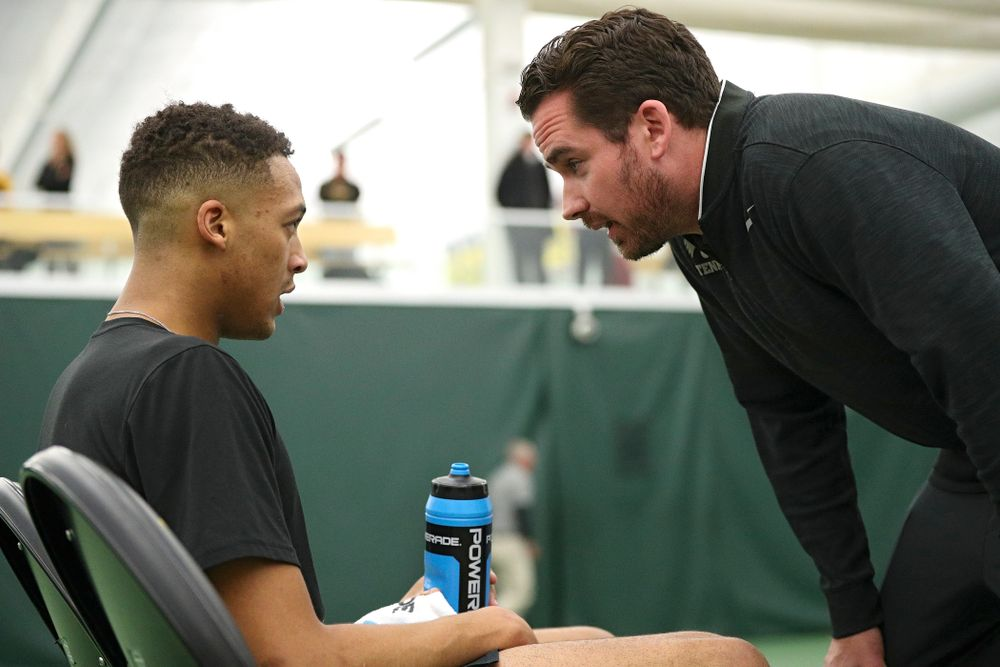 Mellecker Family Head Men's Tennis Coach Ross Wilson (right) talks with Oliver Okonkwo during his singles match at the Hawkeye Tennis and Recreation Complex in Iowa City on Friday, February 14, 2020. (Stephen Mally/hawkeyesports.com)