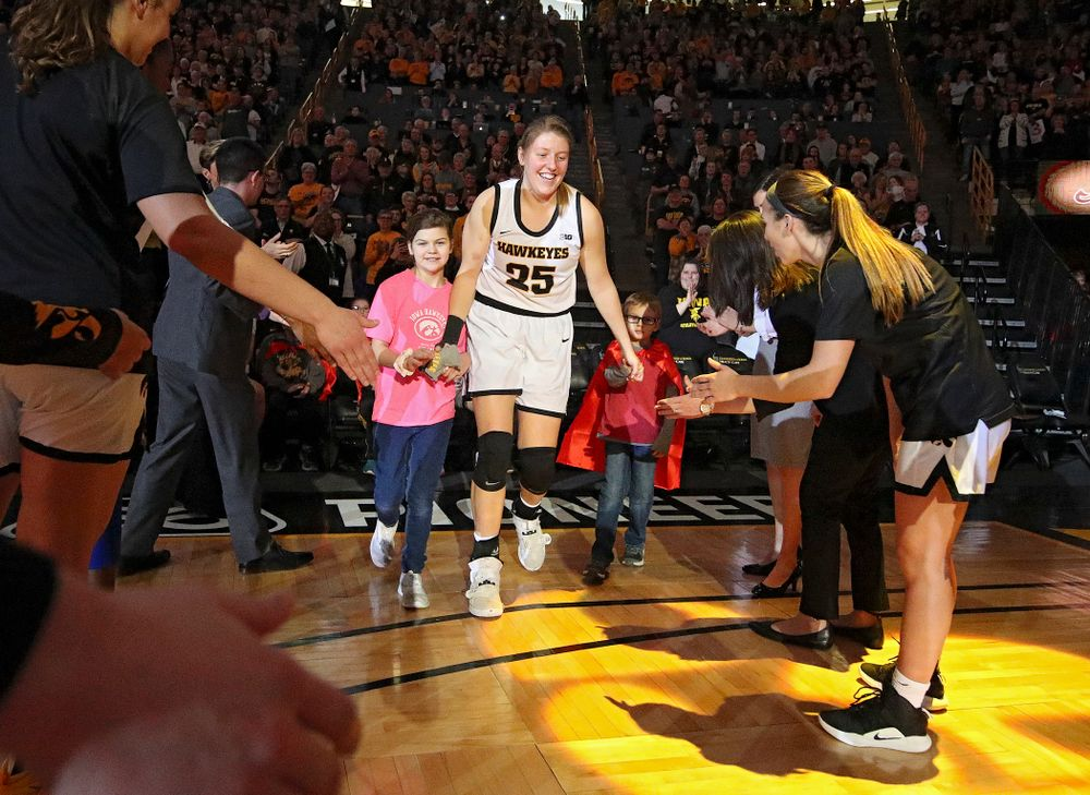 Iowa Hawkeyes forward Monika Czinano (25) is introduced with two Go Red for Women Movement Heart Champions before the start of their game at Carver-Hawkeye Arena in Iowa City on Sunday, January 26, 2020. (Stephen Mally/hawkeyesports.com)