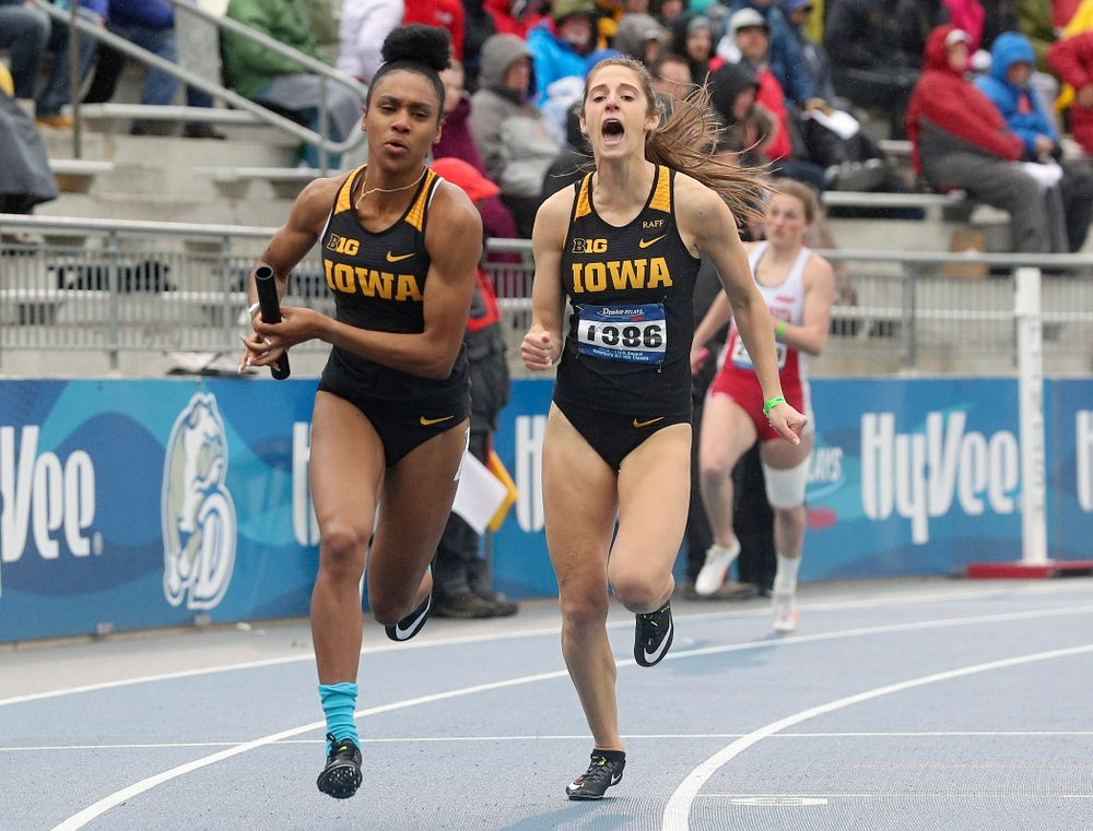 Iowa's Talia Buss (right) shouts after handing off the baton to Briana Guillory as they run the women's sprint medley relay event during the third day of the Drake Relays at Drake Stadium in Des Moines on Saturday, Apr. 27, 2019. (Stephen Mally/hawkeyesports.com)