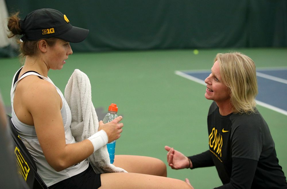 Iowa's Elise Van Heuvelen (from left) talks with head coach Sasha Schmid during her singles match at the Hawkeye Tennis and Recreation Complex in Iowa City on Sunday, February 23, 2020. (Stephen Mally/hawkeyesports.com)