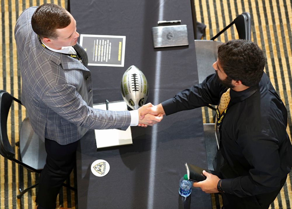 Conor Boffeli (from left), former Iowa offensive lineman, shakes hands with defensive end A.J. Epenesa as former players meet with members of the current Hawkeye Football team during a networking event at Kinnick Stadium in Iowa City on Thursday, Jun 6, 2019. (Stephen Mally/hawkeyesports.com)