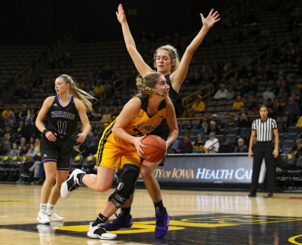 Iowa guard Kate Martin (20) is fouled as she drives in during the first quarter of their game against Winona State at Carver-Hawkeye Arena in Iowa City on Sunday, Nov 3, 2019. (Stephen Mally/hawkeyesports.com)