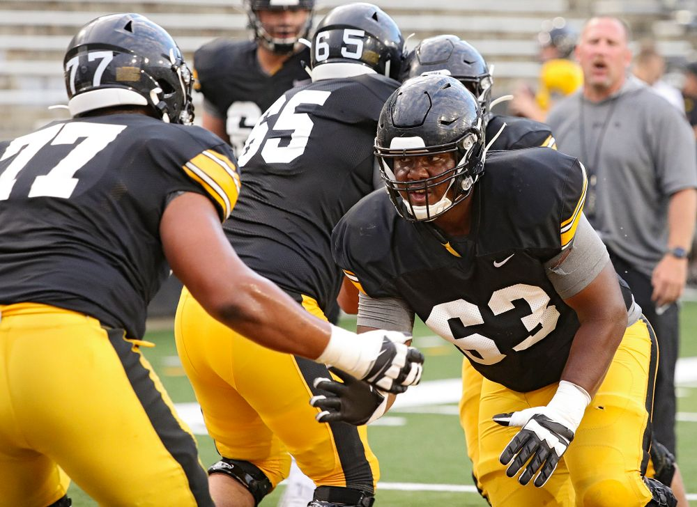 Iowa Hawkeyes offensive lineman Justin Britt (63) eyes offensive lineman Alaric Jackson (77) as they run a drill during Fall Camp Practice No. 12 at Kinnick Stadium in Iowa City on Thursday, Aug 15, 2019. (Stephen Mally/hawkeyesports.com)