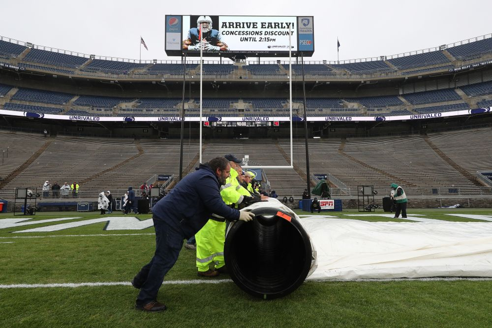 The grounds crew rolls up the tarps before the Iowa Hawkeyes game against the Penn State Nittany Lions Saturday, October 27, 2018 at Beaver Stadium in University Park, Pa. (Brian Ray/hawkeyesports.com)