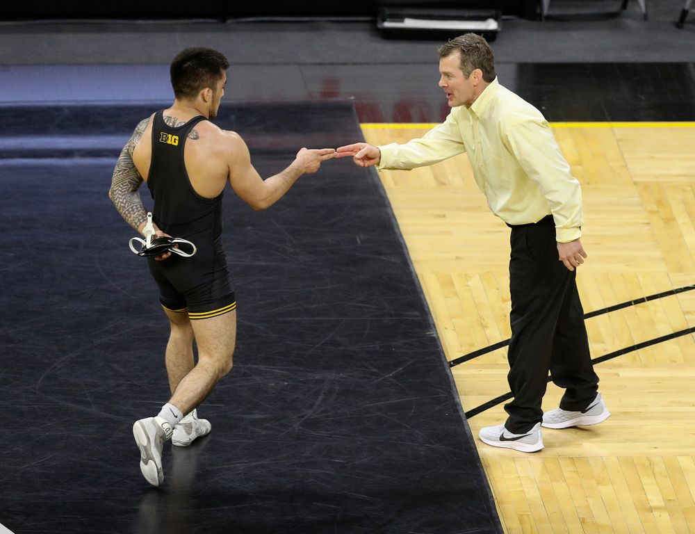 Iowa's Pat Lugo (from left) celebrates his 6-1 win with head coach Tom Brands during their dual at Carver-Hawkeye Arena in Iowa City on Friday, January 31, 2020. (Stephen Mally/hawkeyesports.com)