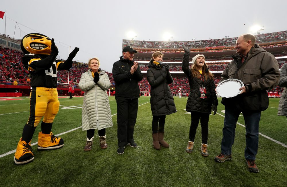 Iowa hero Katie Gudenkauf stands with Iowa Governor Kim Reynolds and Henry B. and Patricia B. Tippie Director of Athletics Chair Gary Barta as she is honored at half-time of the Iowa Hawkeyes game against the Nebraska Cornhuskers Friday, November 29, 2019 at Memorial Stadium in Lincoln, Neb. (Brian Ray/hawkeyesports.com)