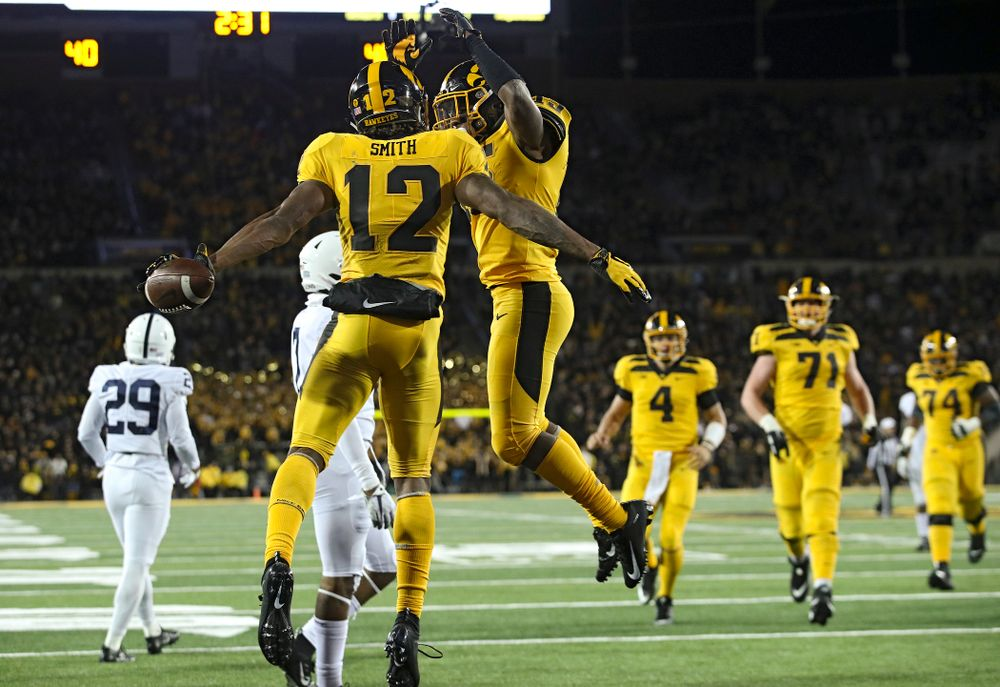 Iowa Hawkeyes wide receiver Brandon Smith (12) celebrates his touchdown reception with running back Tyler Goodson (15) during the fourth quarter of their game at Kinnick Stadium in Iowa City on Saturday, Oct 12, 2019. (Stephen Mally/hawkeyesports.com)