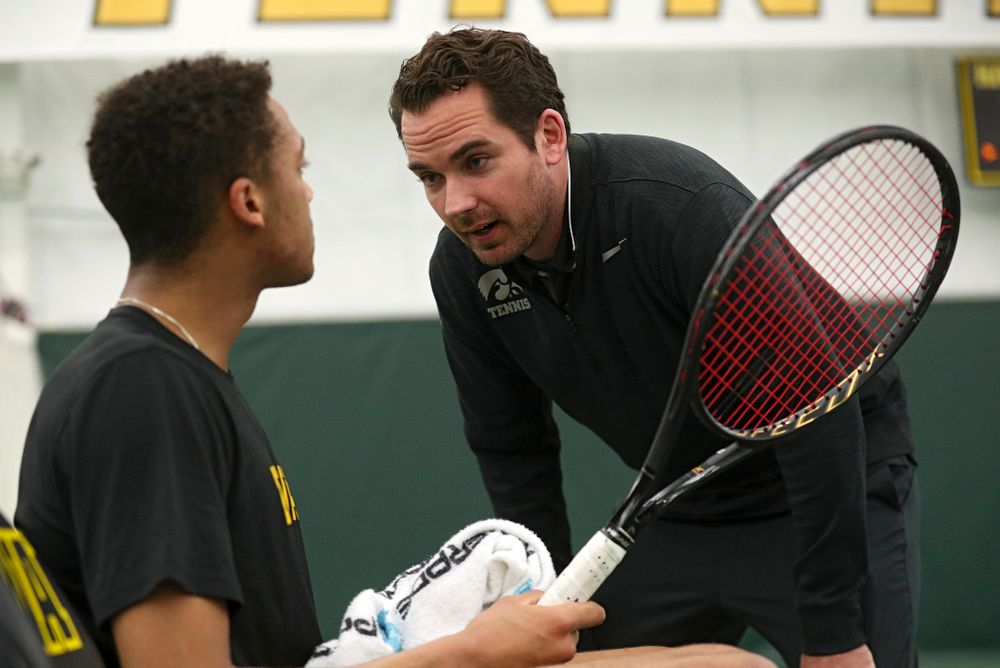 Mellecker Family Head Men's Tennis Coach Ross Wilson (right) talks with Oliver Okonkwo during his singles match at the Hawkeye Tennis and Recreation Complex in Iowa City on Friday, March 6, 2020. (Stephen Mally/hawkeyesports.com)