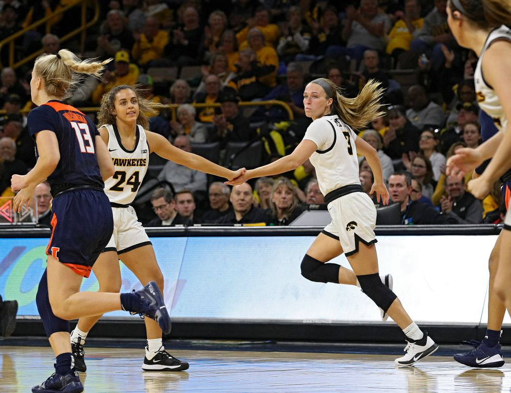 Iowa Hawkeyes guard Gabbie Marshall (24) gives guard Makenzie Meyer (3) a high-five after Meyer made a 3-pointer during the third quarter of their game at Carver-Hawkeye Arena in Iowa City on Tuesday, December 31, 2019. (Stephen Mally/hawkeyesports.com)