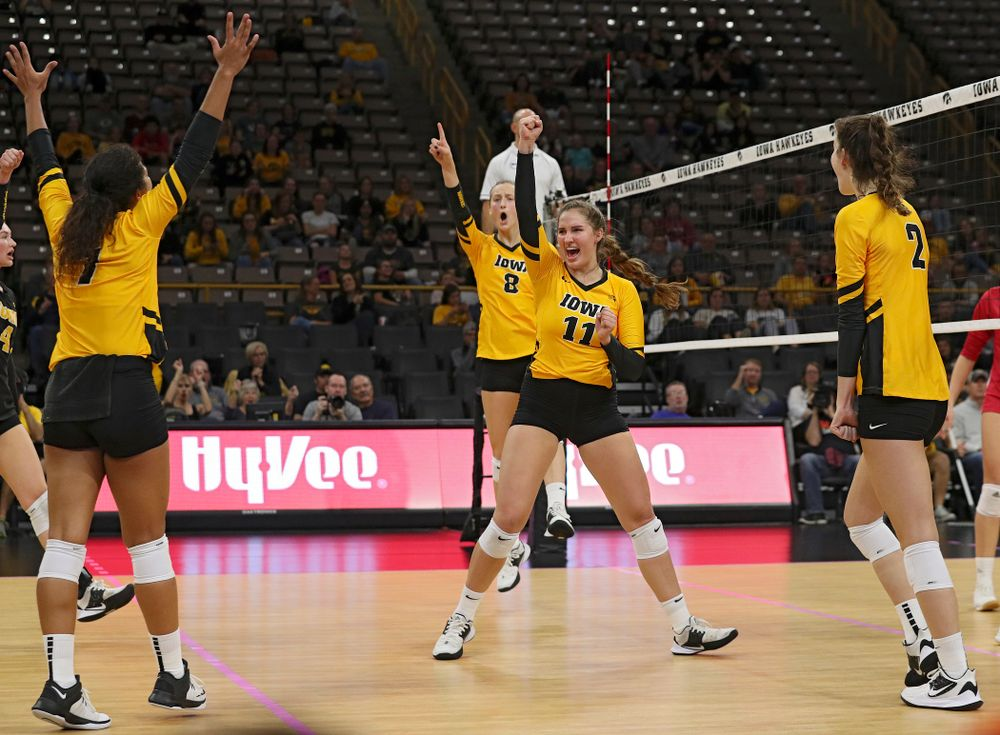 Iowa's Brie Orr (7), Kyndra Hansen (8), Blythe Rients (11), and Courtney Buzzerio (2) celebrate a score during their match at Carver-Hawkeye Arena in Iowa City on Sunday, Oct 20, 2019. (Stephen Mally/hawkeyesports.com)
