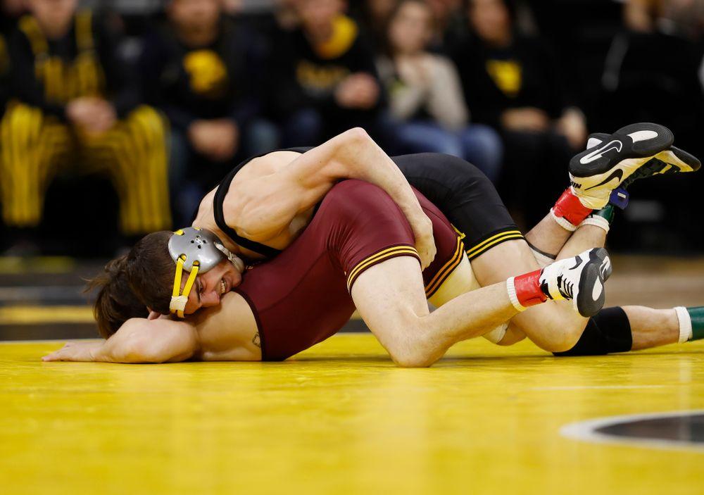 Iowa's Paul Glynn wrestles Minnesota's Mitch McKee at 133 pounds