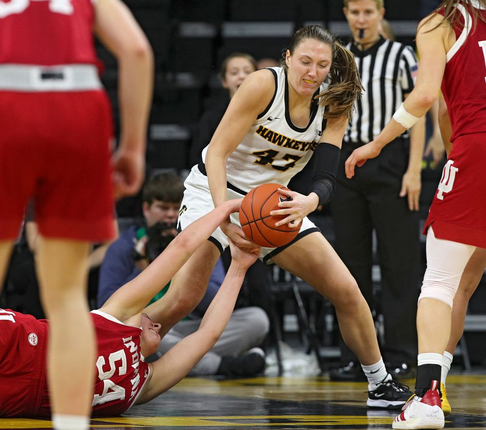 Iowa Hawkeyes forward Amanda Ollinger (43) and Indiana Hoosiers forward Mackenzie Holmes (54) hang on to a held ball during the fourth quarter of their game at Carver-Hawkeye Arena in Iowa City on Sunday, January 12, 2020. (Stephen Mally/hawkeyesports.com)