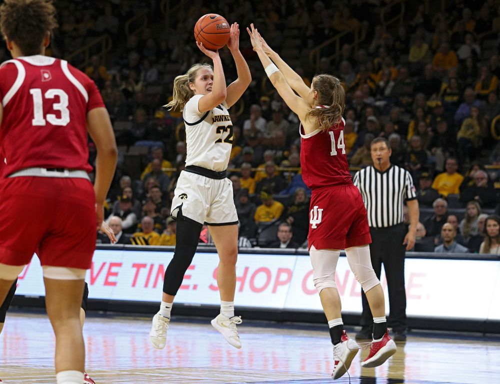 Iowa Hawkeyes guard Kathleen Doyle (22) makes a basket over the hands of Indiana Hoosiers guard Ali Patberg (14) during the third quarter of their game at Carver-Hawkeye Arena in Iowa City on Sunday, January 12, 2020. (Stephen Mally/hawkeyesports.com)