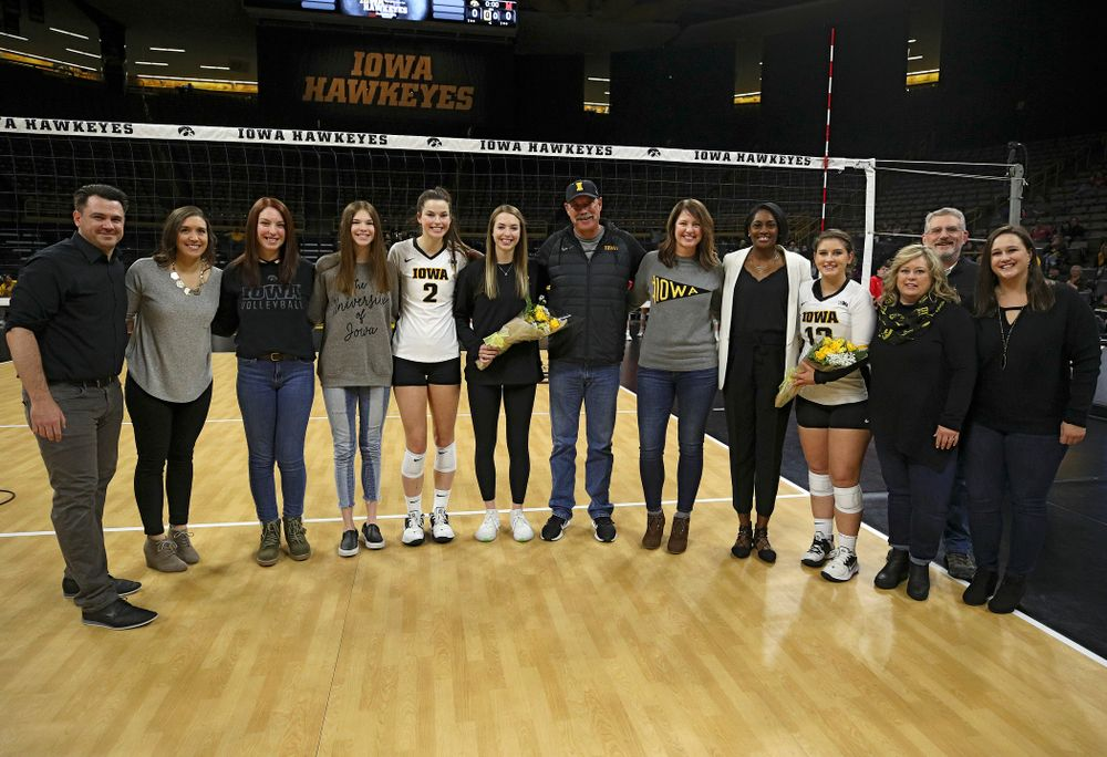 Iowa's Meghan Buzzerio (5) and Emily Bushman (12) are honored on the court with their families and the coaching staff on Senior Day before their match at Carver-Hawkeye Arena in Iowa City on Saturday, Nov 30, 2019. (Stephen Mally/hawkeyesports.com)