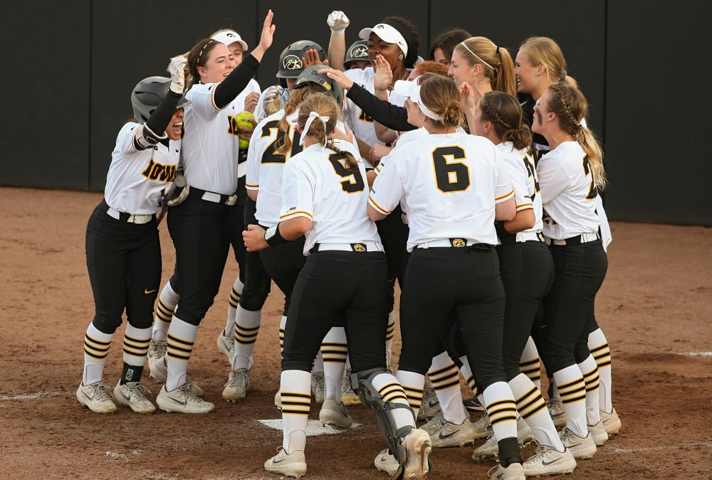 Iowa designated player Miranda Schulte (20) is greeted by teammates at home plate after hitting a home run during the sixth inning of their game against Ohio State at Pearl Field in Iowa City on Friday, May. 3, 2019. (Stephen Mally/hawkeyesports.com)