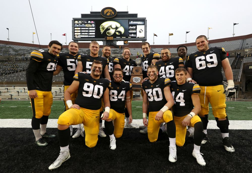 The Iowa Hawkeyes celebrate with the Heroes game trophy following their win against the Nebraska Cornhuskers Friday, November 23, 2018 at Kinnick Stadium. (Brian Ray/hawkeyesports.com)