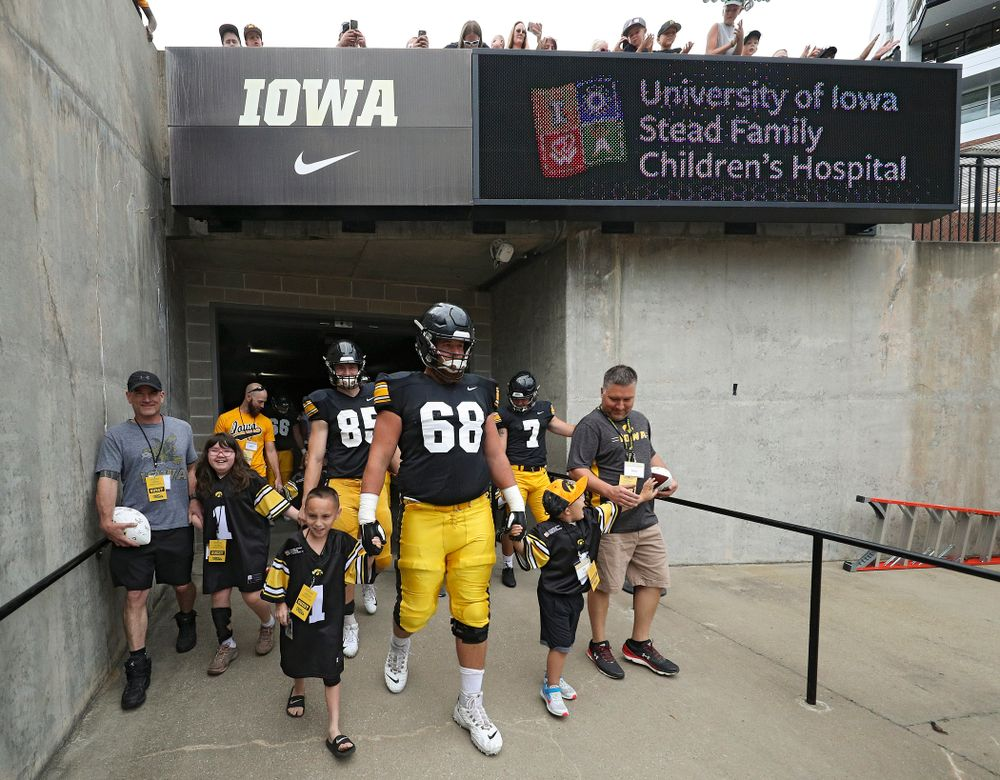 Kid Captains Skylar Hardee (left) and Jeg Weets (right) walk with Iowa Hawkeyes offensive lineman Landan Paulsen (68) prepare to swarm as they exit the tunnel during Kids Day at Kinnick Stadium in Iowa City on Saturday, Aug 10, 2019. (Stephen Mally/hawkeyesports.com)