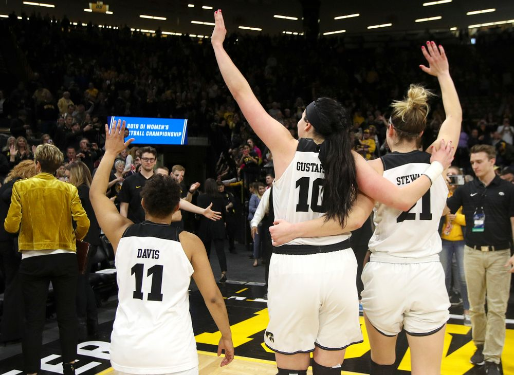 Iowa Hawkeyes guard Tania Davis (11), center Megan Gustafson (10), and forward Hannah Stewart (21) wave to the crowd after winning their second round game in the 2019 NCAA Women's Basketball Tournament at Carver Hawkeye Arena in Iowa City on Sunday, Mar. 24, 2019. (Stephen Mally for hawkeyesports.com)