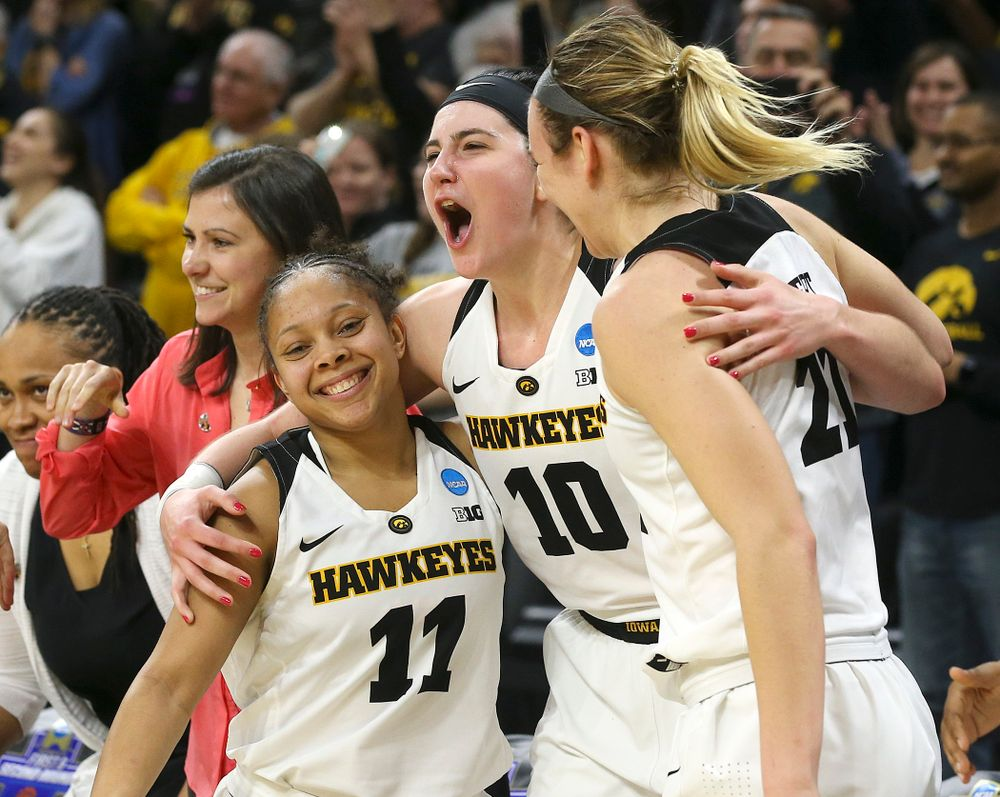 Iowa Hawkeyes guard Tania Davis (11), center Megan Gustafson (10), and forward Hannah Stewart (21) hug in the closing seconds of the fourth quarter of their second round game in the 2019 NCAA Women's Basketball Tournament at Carver Hawkeye Arena in Iowa City on Sunday, Mar. 24, 2019. (Stephen Mally for hawkeyesports.com)