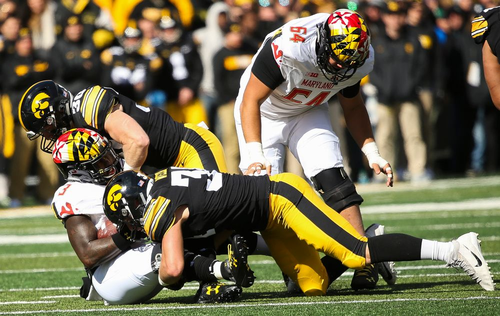 Iowa Hawkeyes defensive back Jake Gervase (30) and Iowa Hawkeyes linebacker Kristian Welch (34) make a tackle during a game against Maryland at Kinnick Stadium on October 20, 2018. (Tork Mason/hawkeyesports.com)