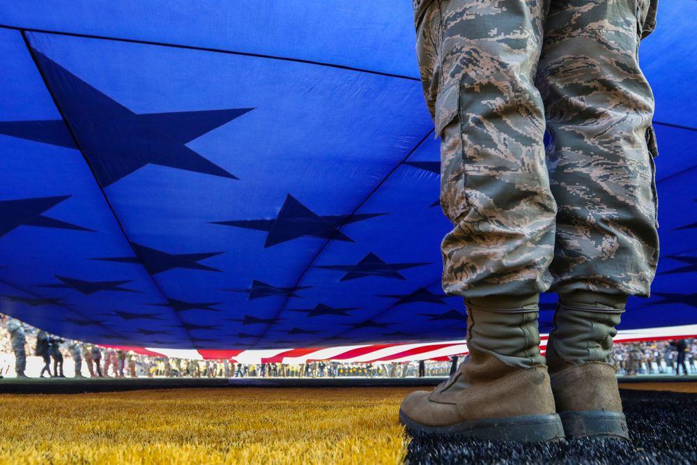 A U.S. Service Member helps hold an American flag during Iowa football vs Minnesota on Saturday, November 16, 2019 at Kinnick Stadium. (Lily Smith/hawkeyesports.com)