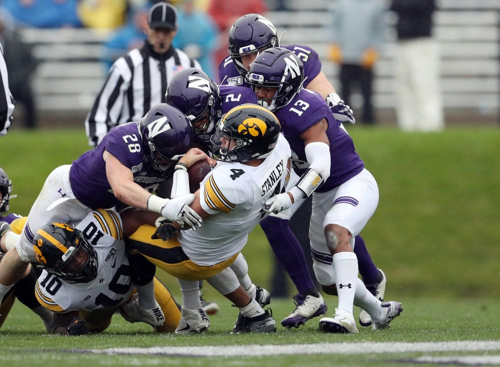 Iowa Hawkeyes quarterback Nate Stanley (4) picks up a first down against the Northwestern Wildcats Saturday, October 26, 2019 at Ryan Field in Evanston, Ill. (Brian Ray/hawkeyesports.com)