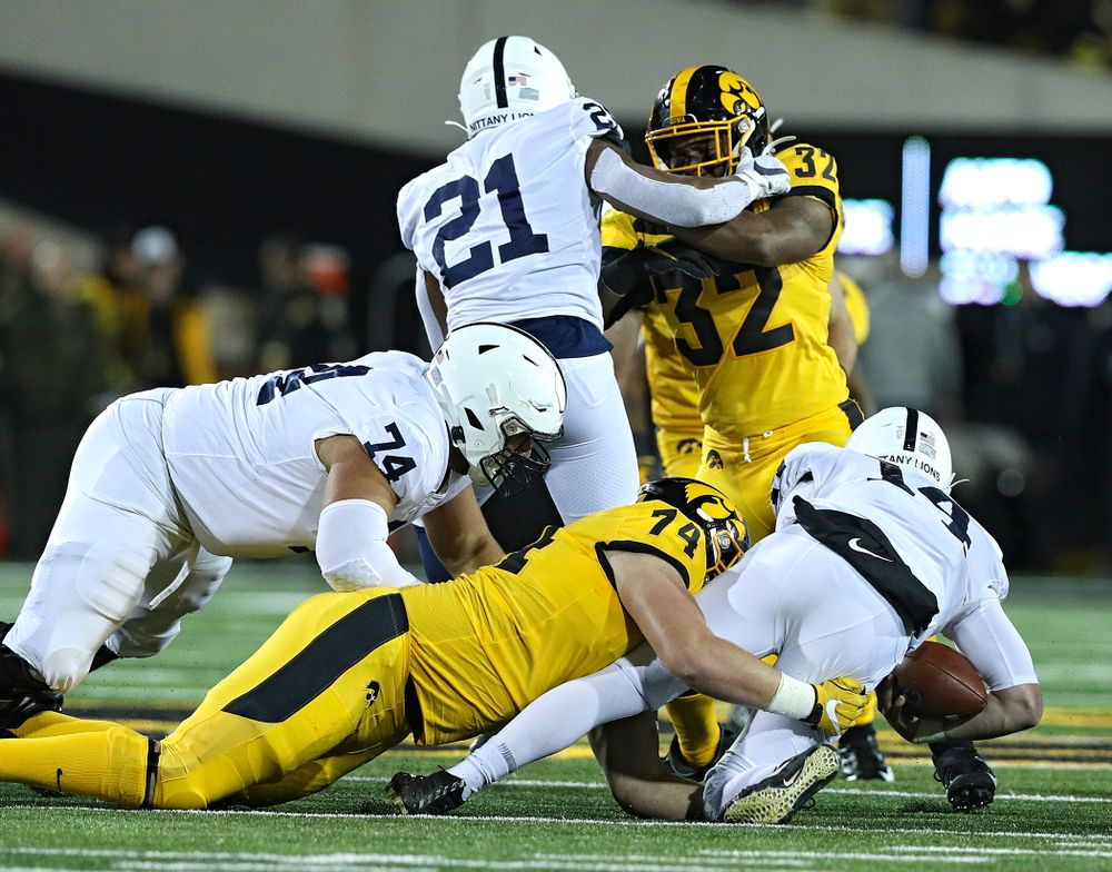 Iowa Hawkeyes defensive lineman Austin Schulte (74) brings down Penn State Nittany Lions quarterback Sean Clifford (14) for a loss during the first quarter of their game at Kinnick Stadium in Iowa City on Saturday, Oct 12, 2019. (Stephen Mally/hawkeyesports.com)