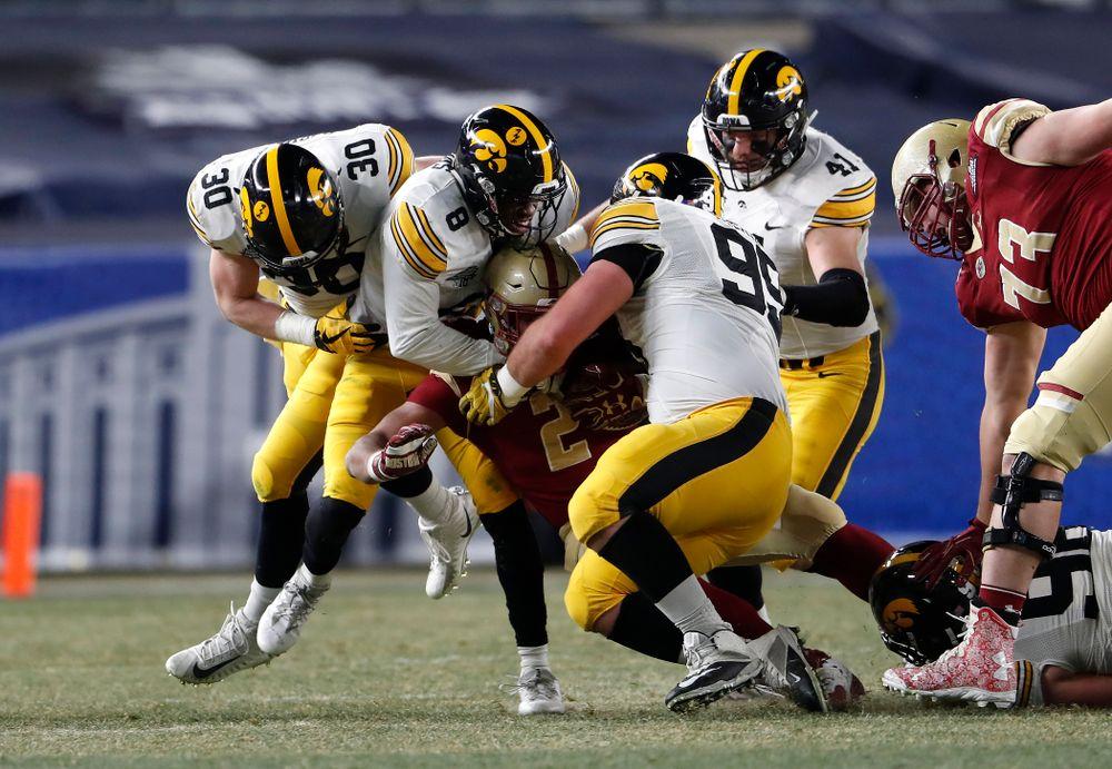 Iowa Hawkeyes defensive back Matt Hankins (8) and defensive lineman Cedrick Lattimore (95)