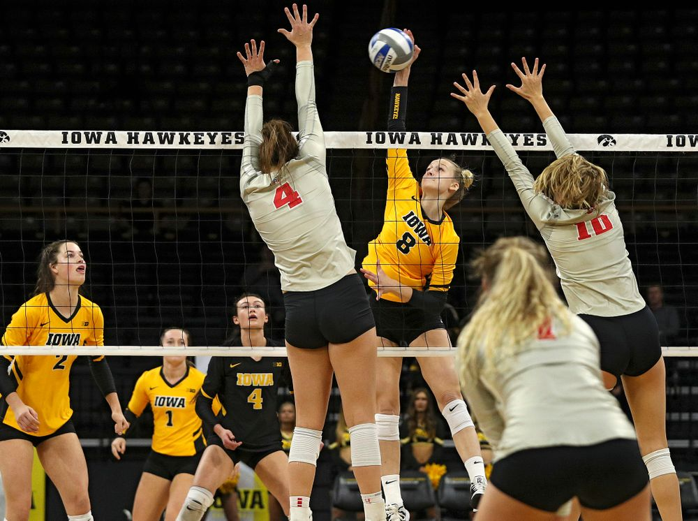 Iowa's Kyndra Hansen (8) gets a kill between two players during the first set of their match at Carver-Hawkeye Arena in Iowa City on Friday, Nov 29, 2019. (Stephen Mally/hawkeyesports.com)