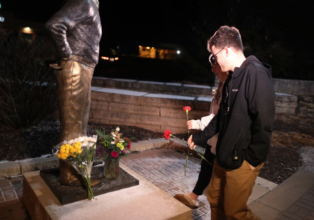 Mourners lay flowers at the statue of former Hawkeye Football Head Coach Hayden Fry Tuesday, December 17, 2019 in Coralville. Fry passed away on Tuesday at the age of 90. (Brian Ray/hawkeyesports.com)