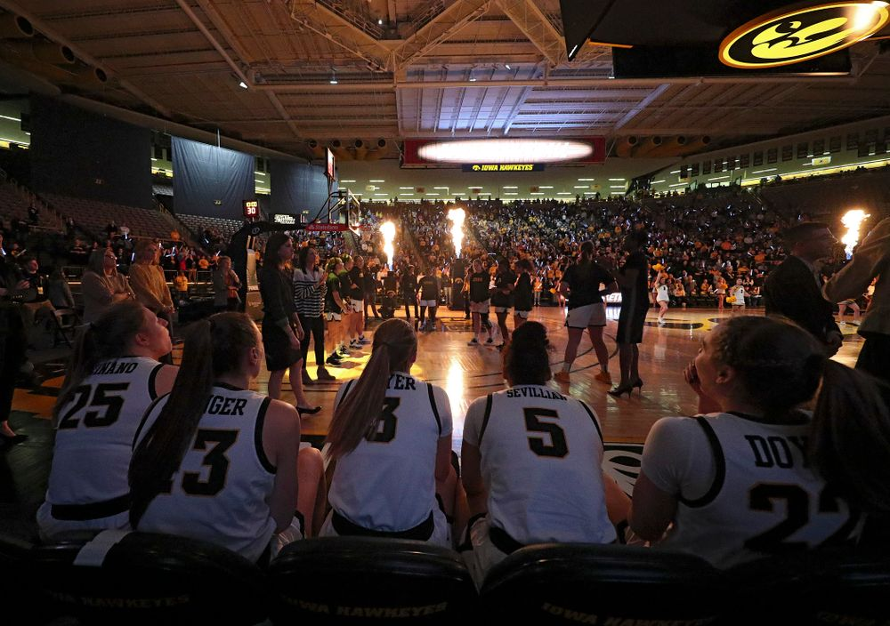 Iowa Hawkeyes forward Monika Czinano (25), forward Amanda Ollinger (43), guard Makenzie Meyer (3), guard Alexis Sevillian (5), and guard Kathleen Doyle (22) sit on the bench as they wait to be introduced before the game at Carver-Hawkeye Arena in Iowa City on Thursday, February 6, 2020. (Stephen Mally/hawkeyesports.com)