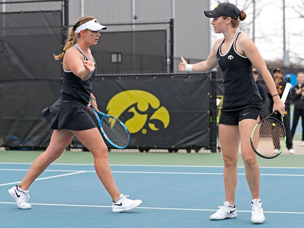 Iowa's Ashleigh Jacobs (from left) and Elise van Heuvelen Treadwell celebrate a score during their doubles match against Rutgers at the Hawkeye Tennis and Recreation Complex in Iowa City on Friday, Apr. 5, 2019. (Stephen Mally/hawkeyesports.com)