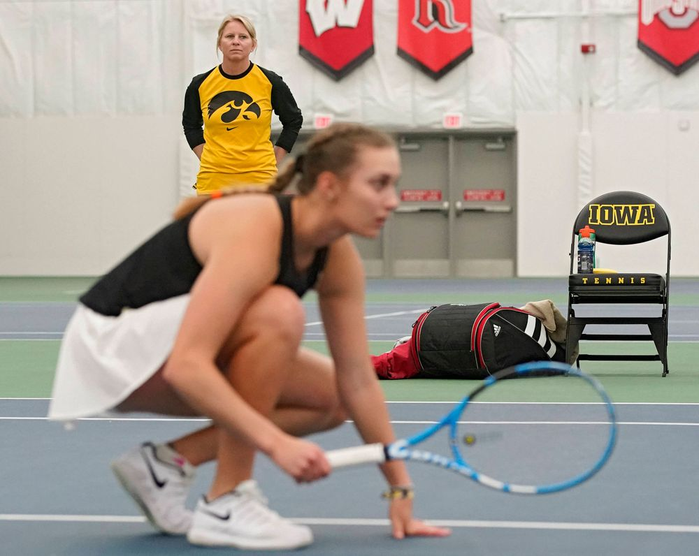 Iowa head coach Sasha Schmid (top) looks on as Ashleigh Jacobs ducks during a serve in their doubles match against Indiana at the Hawkeye Tennis and Recreation Complex in Iowa City on Sunday, Mar. 31, 2019. (Stephen Mally/hawkeyesports.com)