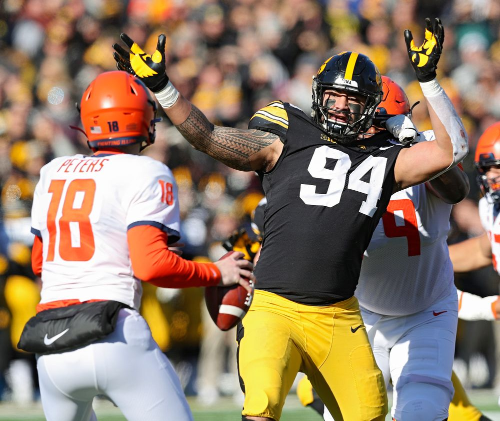 Iowa Hawkeyes defensive end A.J. Epenesa (94) closes in on Illinois Fighting Illini quarterback Brandon Peters (18) during the first quarter of their game at Kinnick Stadium in Iowa City on Saturday, Nov 23, 2019. (Stephen Mally/hawkeyesports.com)