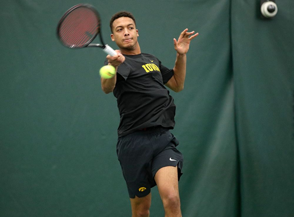 Iowa's Oliver Okonkwo hits a shot during his match against Marquette at the Hawkeye Tennis and Recreation Complex in Iowa City on Saturday, January 25, 2020. (Stephen Mally/hawkeyesports.com)