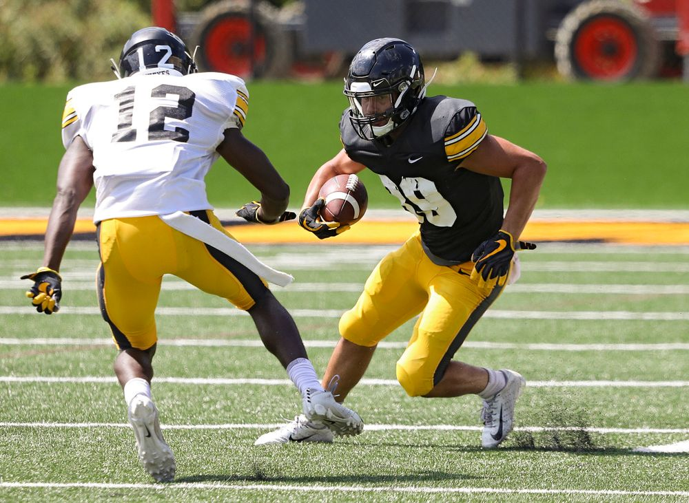 Iowa Hawkeyes wide receiver Nico Ragaini (89) avoids defensive back D.J. Johnson (12) during Fall Camp Practice #5 at the Hansen Football Performance Center in Iowa City on Tuesday, Aug 6, 2019. (Stephen Mally/hawkeyesports.com)