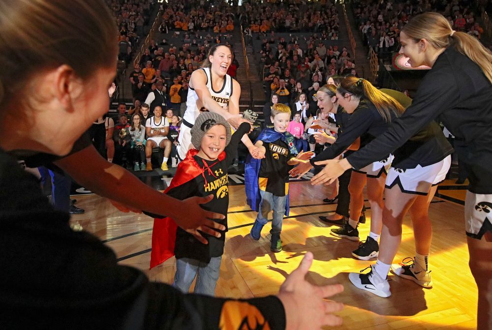 Iowa Hawkeyes forward Amanda Ollinger (43) is introduced with two Go Red for Women Movement Heart Champions before the start of their game at Carver-Hawkeye Arena in Iowa City on Sunday, January 26, 2020. (Stephen Mally/hawkeyesports.com)