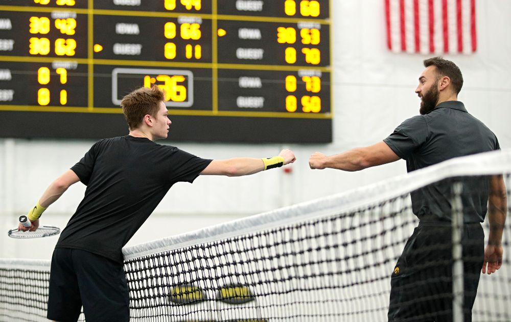 Iowa's Jason Kerst (from left) gets a fist bump from assistant coach Lloyd Bruce-Burgess after winning his match against Marquette at the Hawkeye Tennis and Recreation Complex in Iowa City on Saturday, January 25, 2020. (Stephen Mally/hawkeyesports.com)