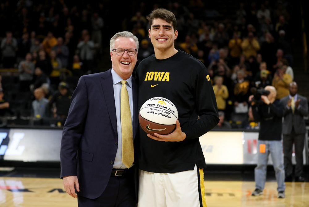Iowa Hawkeyes forward Luka Garza (55) receives a ball commemorating his 1000th point from head coach Fran McCaffery before their game against the Minnesota Golden Gophers Monday, December 9, 2019 at Carver-Hawkeye Arena. (Brian Ray/hawkeyesports.com)