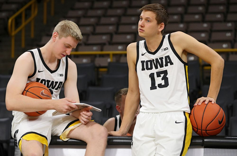 Iowa Hawkeyes forward Michael Baer (0) reads a media guide as guard Austin Ash (13) looks on during Iowa Men's Basketball Media Day at Carver-Hawkeye Arena in Iowa City on Wednesday, Oct 9, 2019. (Stephen Mally/hawkeyesports.com)