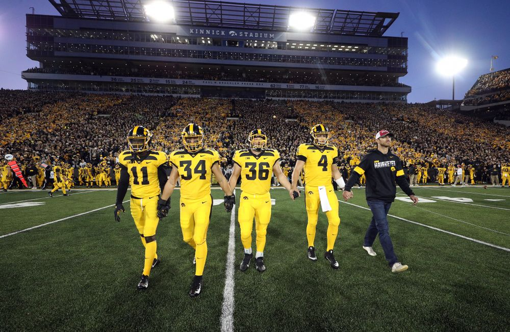 Iowa Hawkeyes captains defensive back Michael Ojemudia (11), linebacker Kristian Welch (34), fullback Brady Ross (36), and quarterback Nate Stanley (4), walk with honorary captain Ricky Stanzi before their game against the Penn State Nittany Lions Saturday, October 12, 2019 at Kinnick Stadium. (Brian Ray/hawkeyesports.com)