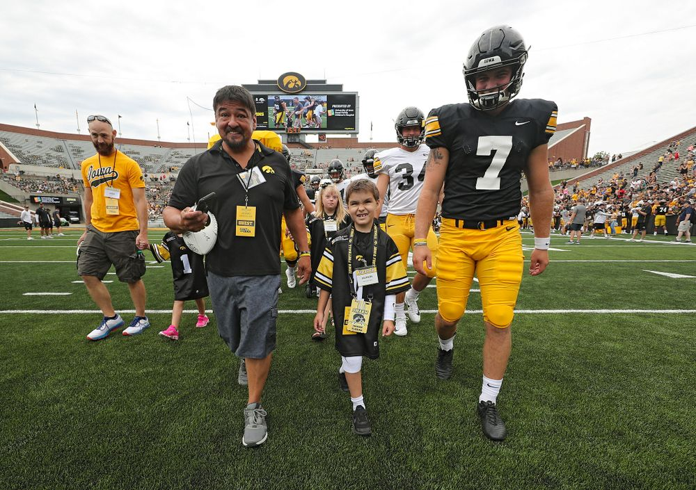 Kid Captain Jackson Tijerina swarms with Iowa Hawkeyes punter Colten Rastetter (7) during Kids Day at Kinnick Stadium in Iowa City on Saturday, Aug 10, 2019. (Stephen Mally/hawkeyesports.com)