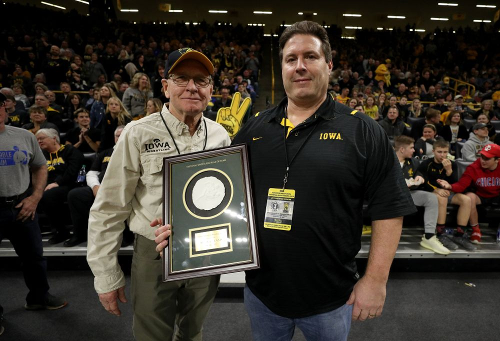 Legendary former head coach Dan Gable presents Mark Reiland with the National Wrestling Hall of Fame Lifetime Service to Wrestling Award during the Iowa Hawkeyes dual against Oklahoma State Sunday, February 23, 2020 at Carver-Hawkeye Arena. (Brian Ray/hawkeyesports.com)