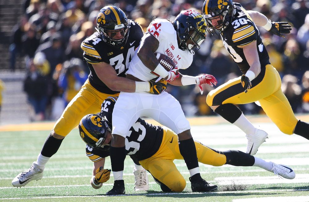 Iowa Hawkeyes linebacker Kristian Welch (34) and Iowa Hawkeyes defensive back Riley Moss (33) make a tackle during a game against Maryland at Kinnick Stadium on October 20, 2018. (Tork Mason/hawkeyesports.com)