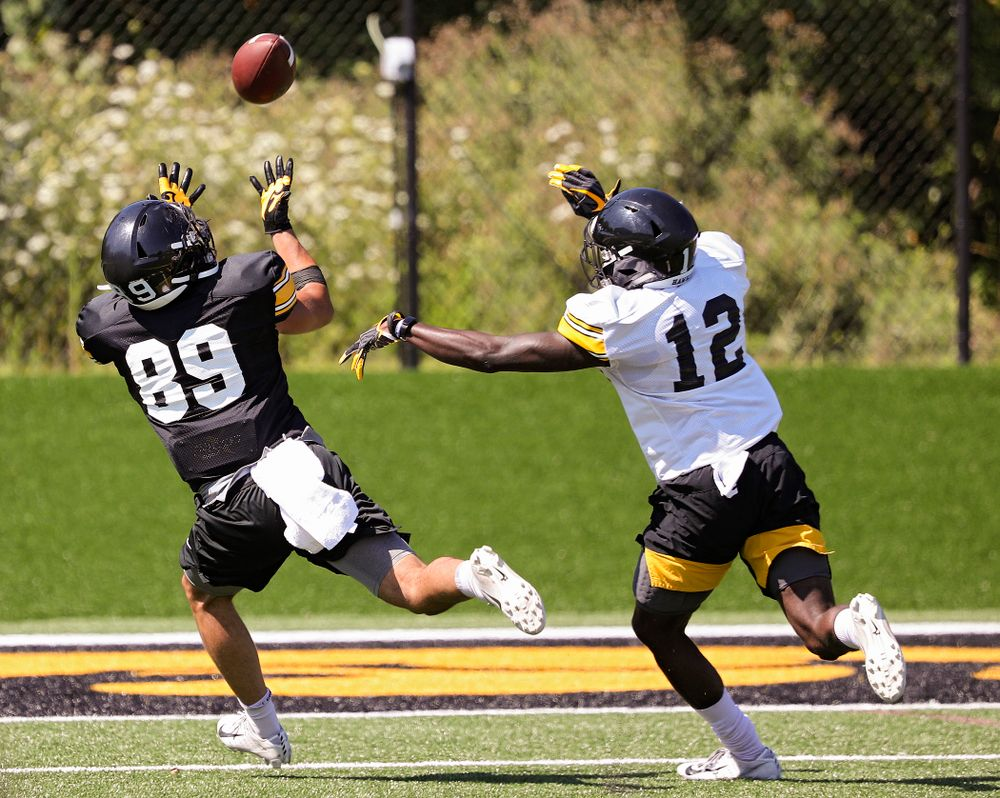 Iowa Hawkeyes wide receiver Nico Ragaini (89) pulls in a pass as defensive back D.J. Johnson (12) gives chase during Fall Camp Practice No. 7 at the Hansen Football Performance Center in Iowa City on Friday, Aug 9, 2019. (Stephen Mally/hawkeyesports.com)